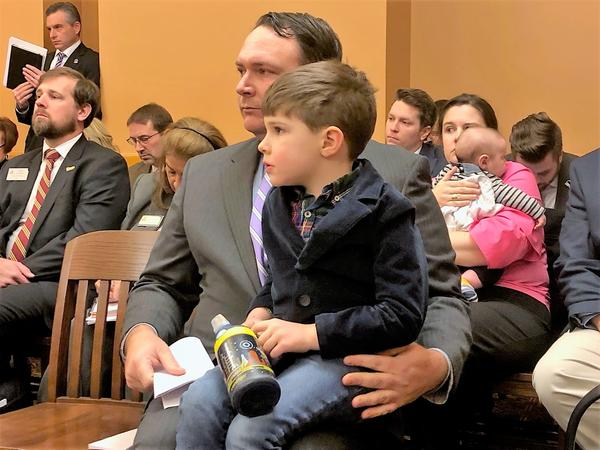 Farmer Tim Franklin, holding his son during a Senate committee hearing, told lawmakers he needs a more affordable health coverage option for his family.