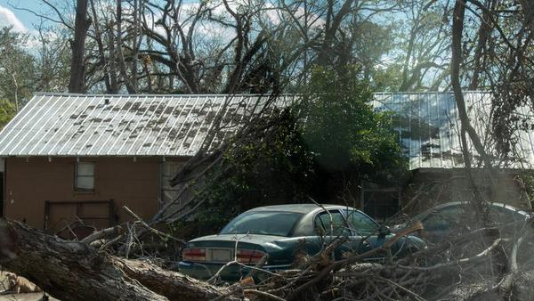 A fallen tree lies in front of a house in Marianna, FL.