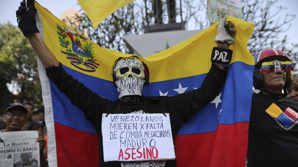 """An anti-government protester on Saturday in Caracas wears a sign that reads, """"Venezuelans die for lack of medicines. Maduro is an assassin."""" Momentum is growing for opposition leader Juan Guaidó, who has called supporters into the streets."""