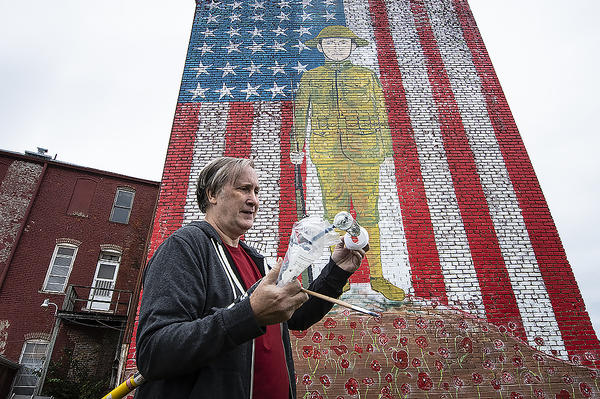 Mural artist Robert Vollrath replaces a paint roller before starting work on his next mural. Behind him, Vollrath's monumental portrait of World War I veteran John Lewis Barkley adorns the old Tamridge House Hotel in downtown Holden, Missouri.