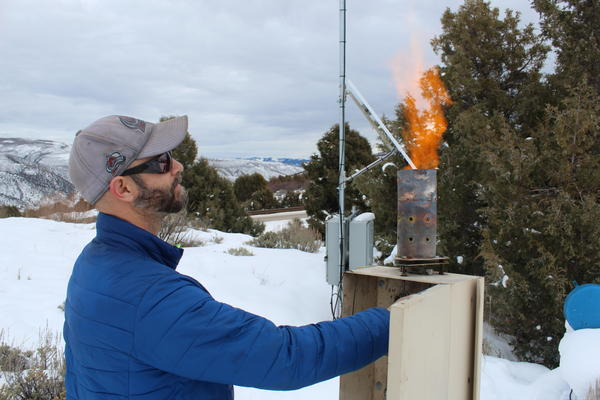 Eric Hjermstad, co-owner of cloud seeding operations company Western Weather Consultants, looks at the flame atop one of his generators near Wolcott, Colorado.