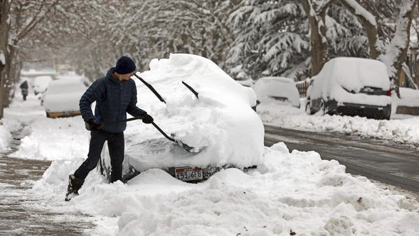 Landon Ainge digs his car out of the snow on Wednesday in Salt Lake City, where a heavy snowfall triggered a rare snow day for many students.
