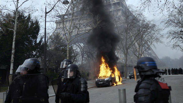 A burning command car belonging to France's anti-terror squad is pictured as riot police take position near the Eiffel Tower.