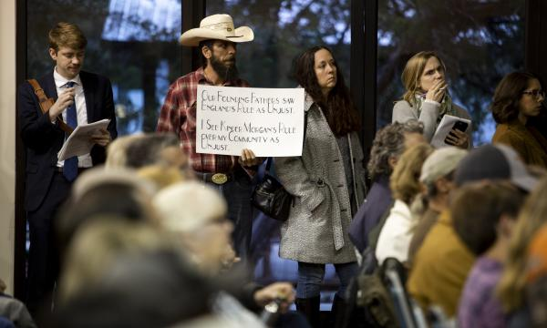 A man holds a sign in protest of a planned natural gas pipeline, during a community meeting at the Wimberley Community Center on Tuesday.