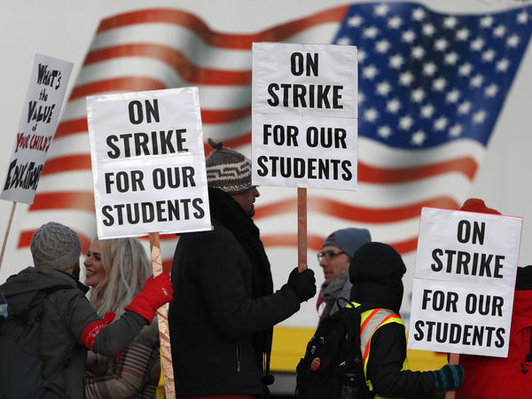 Teachers carry placards as they walk a picket line outside South High School early Monday in Denver. A new lawsuit alleges students with disabilities will be harmed by the strike.