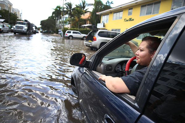 Sandy Garcia sits in her vehicle that was stuck in a flooded street caused by the combination of the lunar orbit which caused seasonal high tides and what many believe is the rising sea levels due to climate change in 2015 in Fort Lauderdale, Florida.