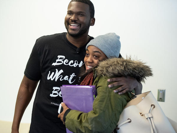 Marc Lavarin, an assistant minister at Alfred Street Baptist Church, hugs Howard University student Mya Thompson after she learns the church's members have paid the $2,500 she owed the university.