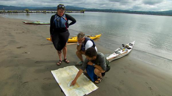 <p>Andrew Emlen, Chris Hathaway and Kyleen Austin study maps on the shore of Lark Island, a sandy dredge spoil east of Tenasillahe Island.</p>