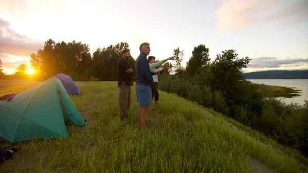 <p>Kyleen Austin points toward Cathlamet, Washington, from their campsite on Lark Island.</p>