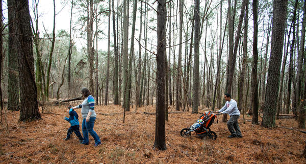 Roan Fields-Moffitt, left, walks with his mother, Desiree Moffitt, second from left, and father, Jacob Fields, right, as he pushes the family's baby twin daughters through a wooded area adjacent to Murdoch Developmental Center in Butner