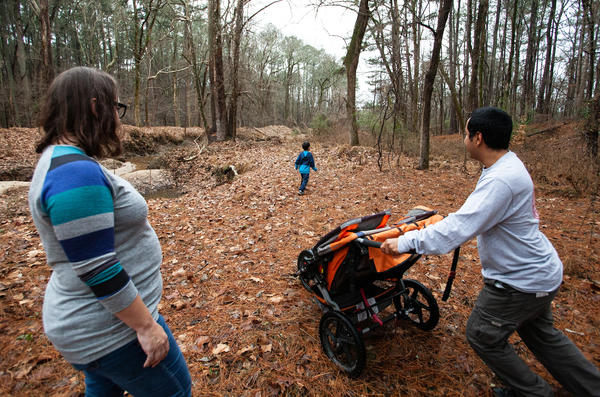 Desiree Moffitt, left, and Jacob Fields, right, watch their son Roan, middle walk through a wooded area adjacent to Murdoch Developmental Center in Butner, N.C. on Thursday, Jan. 3, 2019.