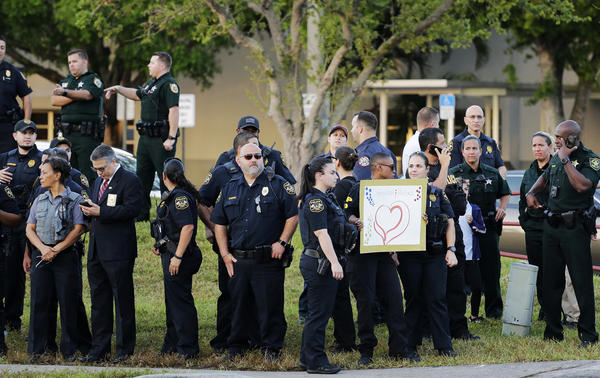 Police stand watch as students returned to class for the first time since a former student opened fire with an assault weapon at Marjory Stoneman Douglas High School in Parkland, Fla., Wednesday, Feb. 28, 2018.