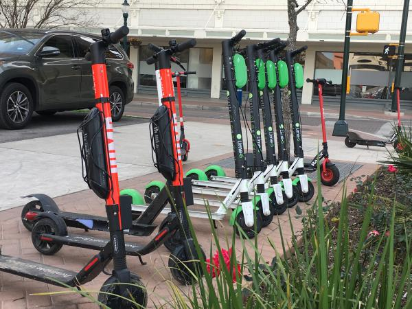 A line of scooters from various companies wait for riders at Houston Street and Main Avenue.