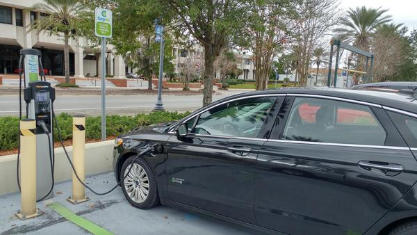 A Ford Fusion Energi charges at the Fidelity office complex on Riverside Ave.