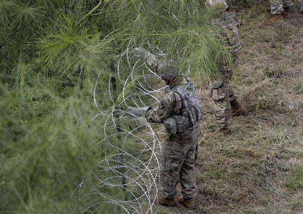 Above: Members of the U.S.military place razor wire along the U.S.-Mexico border near the McAllen-Hidalgo International Bridge, Friday, Nov. 2, 2018.