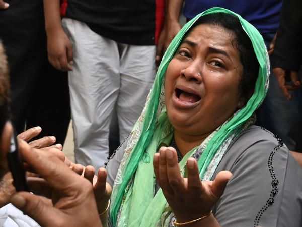 A relative of victims who were killed in a fire mourns.