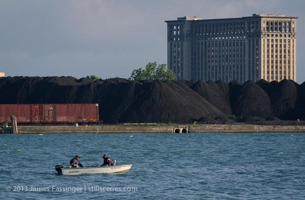 Fisherman on the river with the petroleum coke piles and Michigan Central Station in the background