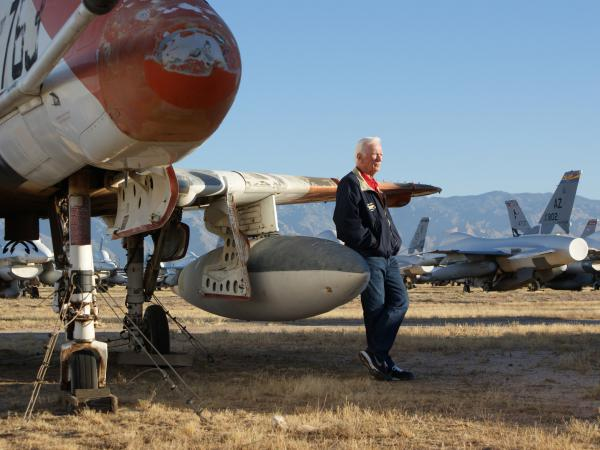 Gene Cernan reflects beside an A-4 Skyhawk from VA113 squadron.