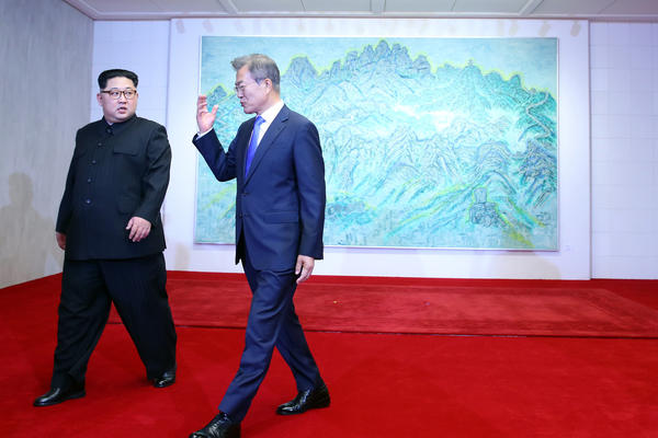 Kim and Moon walk away after posing for photos in front of Bukhansan Peace House in Panmunjom, South Korea.
