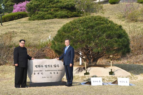 "Kim and Moon pose in front of a stone inscribed ""Peace and Prosperity Are Planted"" as they participate in a tree-planting ceremony next to the Military Demarcation Line that forms the border between the two Koreas."
