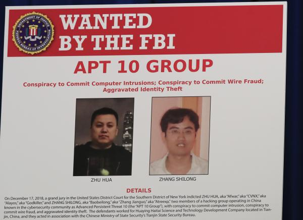 A Justice Department poster shows two Chinese citizens suspected of carrying out an extensive hacking campaign directed at dozens of U.S. tech companies. U.S. law enforcement says such cases are on the rise as China seeks to become a world leader in advanced technologies by 2025.