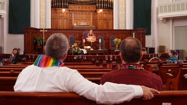 Daron Smith, left, and his husband, Chris Finley, right, worship at a Sunday morning service at Lafayette Park United Methodist Church in St. Louis, Mo. Smith, a lifelong United Methodist, said he feels hopeful ahead of a vote on LGBTQ ordination and same-sex weddings in the church.