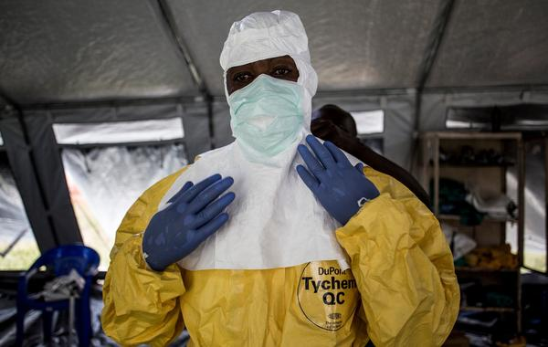 A medical worker puts on protective gear at an Ebola treatment center in Beni in the Democratic Republic of the Congo. Officials want to train workers at all health facilities to take precautions.