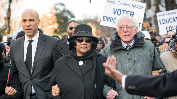 Sens. Cory Booker and Bernie Sanders, seen at a South Carolina NAACP march in January, are two of the 2020 Democratic presidential candidates pressed on the issue of reparations this week.