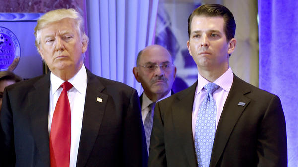 Trump Organization Chief Financial Officer Allen Weisselberg (center) stands behind then-President-elect Donald Trump and his son Don Jr. on Jan. 11, 2017, at Trump Tower in New York.