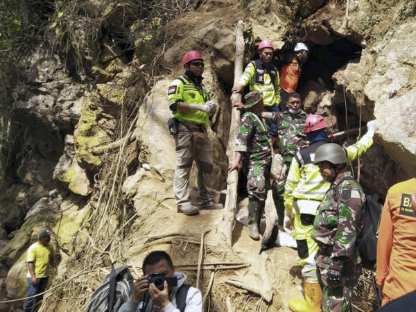 Rescuers stand at the entrance of a collapsed mine in Sulawesi, Indonesia, on Thursday. The shouting of trapped miners ceased on Saturday.