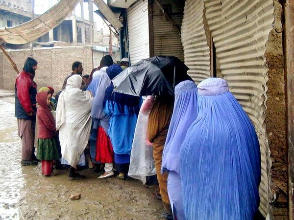 Afghan women wait in line to get bread at subsidized rates at a World Food Program-run bakery in Kabul in 2000.