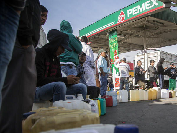 People wait in line to buy gasoline at a station in Morelia, Mexico on January 7, 2019.
