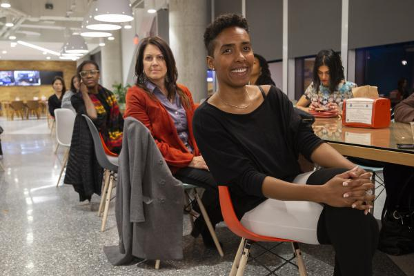 Women listen to DivInc CEO Preston James at the Startup Sistas Happy Hour hosted by Oracle and DivInc.