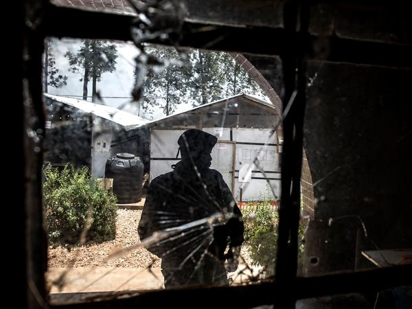 A police officer stands guard in front of a window riddled with bullet holes in an Ebola treatment center, which was attacked in the early hours of the Saturday morning in Butembo. The Democratic Republic of Congo is currently experiencing one of the largest Ebola outbreaks ever.