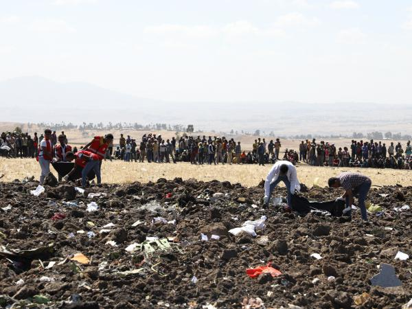 A rescue team collects remains of bodies amid debris at the crash site of Ethiopian Airlines Flight 302 near Bishoftu, a town some 37 miles southeast of Addis Ababa, Ethiopia, on Sunday.