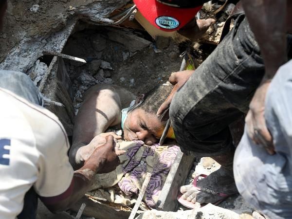 Search and rescue workers are trying to pull a girl out from under piles of concrete rubble after the collapse of a three-story building in Lagos Island, Nigeria, on Wednesday.