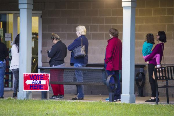 Voters line up to cast ballots at the Travis County Tax Office on the first day of early voting in the midterms Oct. 22.