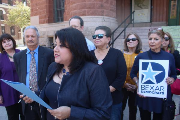 Bexar County Democratic Party Chair Monica Alcantara speaks with members of the party in front of the Bexar County Courthouse.