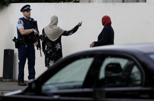 A police officer directs pedestrians near the site of one of the mass shootings at two mosques in Christchurch, New Zealand, on Saturday, March 16.