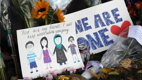 A message card sits among a collection of flowers left at the Christchurch Botanic Gardens in New Zealand on Saturday. A 28-year-old white supremacist accused in the mass shootings at two mosques that left dozens of people dead stood silently before a judge on Saturday.