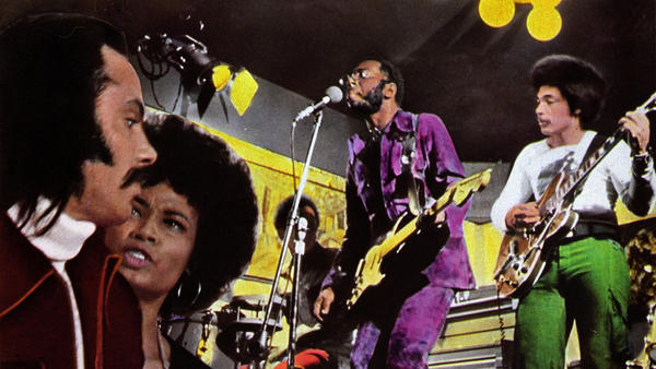 Curtis Mayfield (in purple) performs in a detail from a poster advertising the 1972 film <em>Super Fly</em>, for which Mayfield composed the soundtrack album.