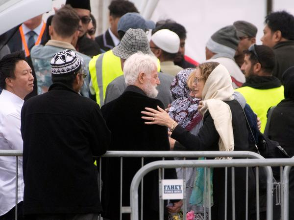 A mourner comforts John Milne (center), the father of 14-year-old Sayyad Milne, during the boy's funeral in Christchurch, New Zealand, on Thursday. Sayyad Milne was one of 50 people killed at two mosques last Friday.