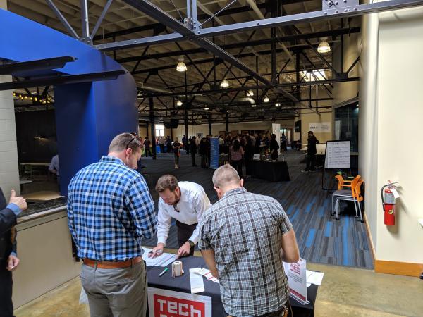 Sean Attwood (center) with San Antonio Economic Development Foundation checks people into the event.