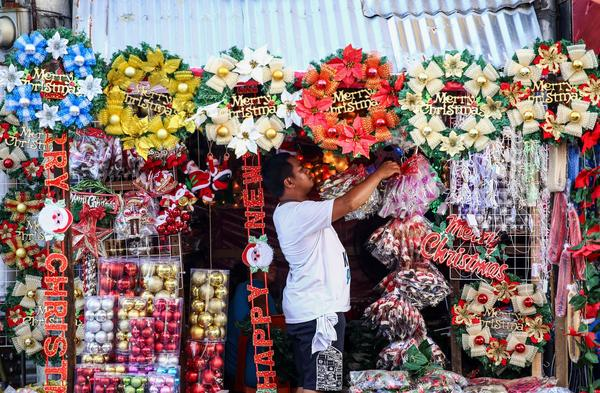 A worker arranges Christmas decorations from a street stall in Manila on Sept. 23. The Philippines, which has the largest Christian population in Asia,  celebrates Christmas season for several months.
