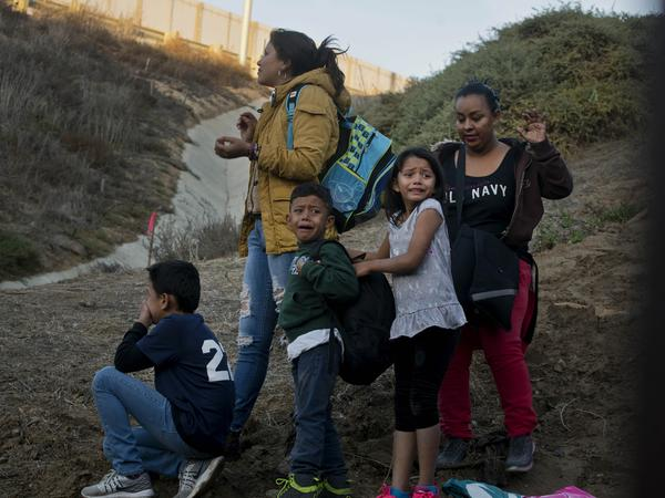 Honduran migrants surrender to the U.S. Border Patrol after crossing a border wall into the United States. According to new federal data, the number of migrants apprehended crossing the border in recent months has surged.