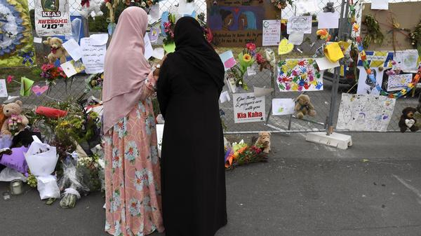 Women look at tributes left at the Linwood Islamic Centre in Christchurch, New Zealand, following the March 15 massacre at two mosques.