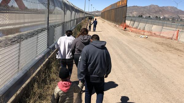 Migrants trudge along the border fence to a waiting bus after turning themselves in to the Border Patrol at the U.S.-Mexico border near El Paso, Texas.