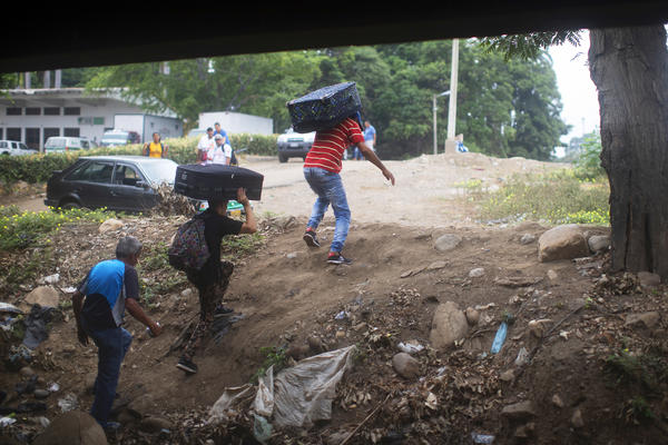 Young men carry luggage from Venezuela into Colombia under the Simón Bolívar International Bridge. Tensions are rising in this border area, where many Venezuelans are seeking refuge and are anxious for change back home.