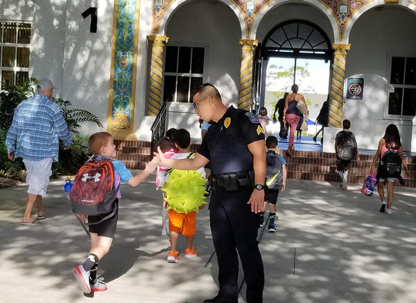 Sergeant Steve Kim of the Sarasota County Schools Police Department with students at Bay Haven School of Basics Plus.