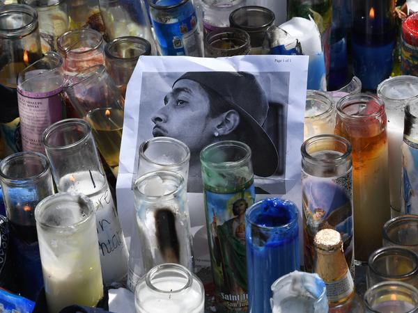 Candles and a photo on display as part of a memorial outside the store owned by rapper and entrepreneur Nipsey Hussle, who was killed there in a shooting on Sunday.